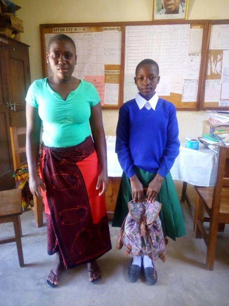 Madre e figlia in posa con il materiale scolastisco consegnato