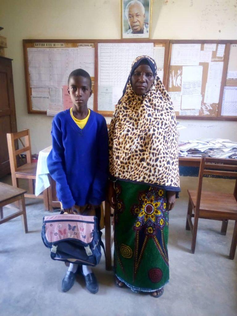 Madre e figlio in posa con il materiale scolastisco consegnato