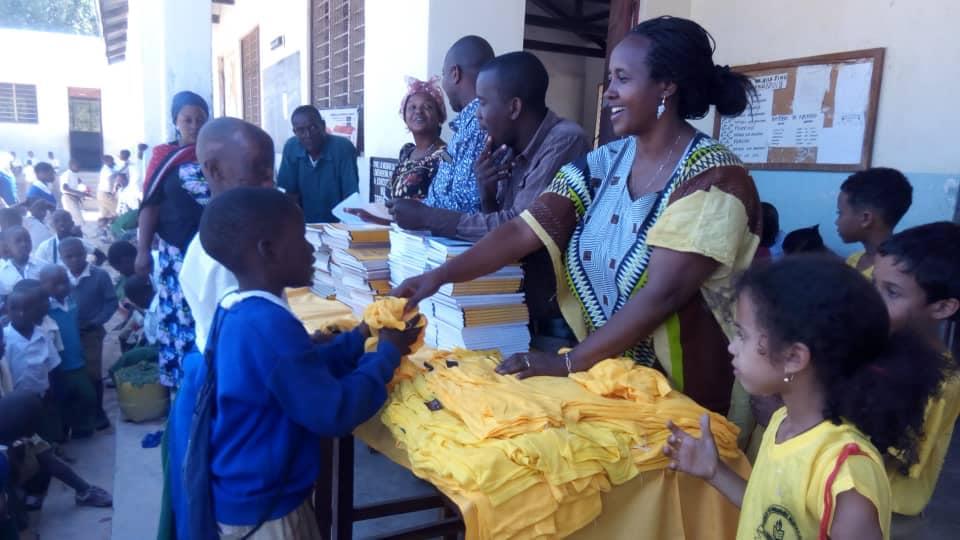 Volontaria che distribuisce materiale scolastico e magliette a bambini in Tanzania