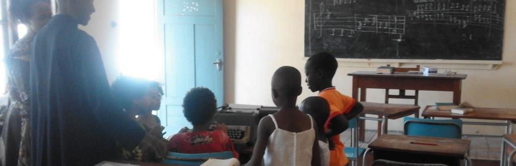 Un gruppo di persone in piedi guarda un bambino che scrive con una macchina da scrivere