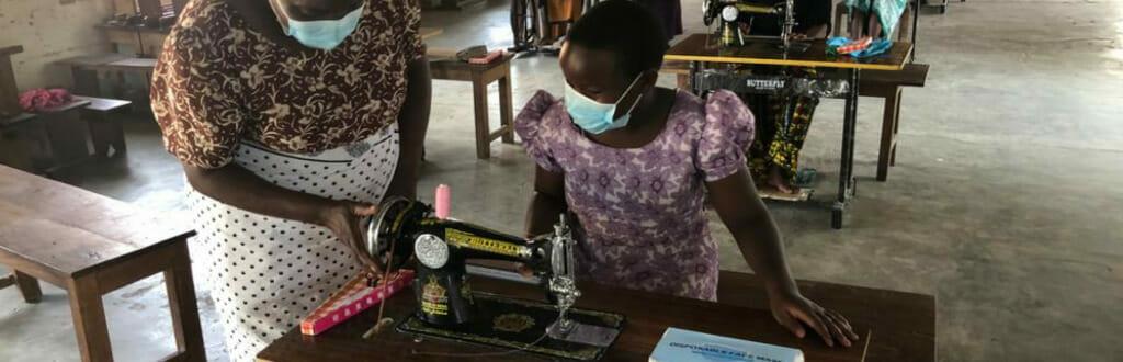 futura sarta ed istruttrice intorno alla macchina da cucire